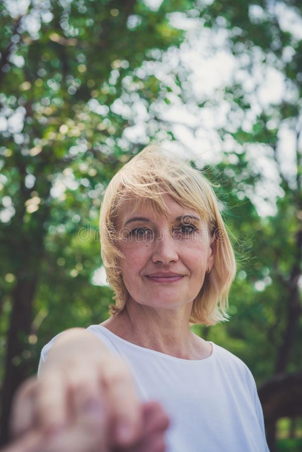 Beautiful senior woman in green park stock photo