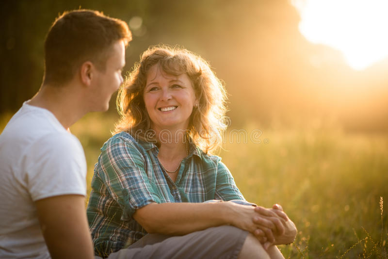 Beautiful senior woman and her adult smiling son sitting in park royalty free stock photos