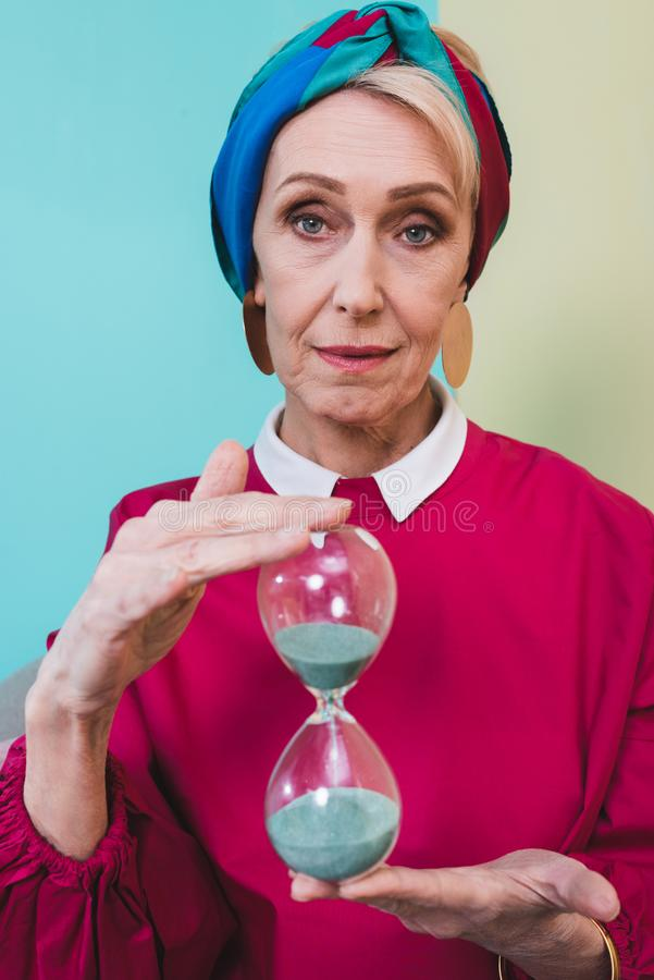 beautiful senior woman holding hourglass stock photos