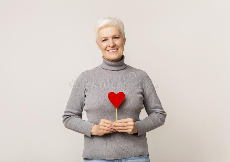 Beautiful senior woman holding paper heart over her chest royalty free stock images