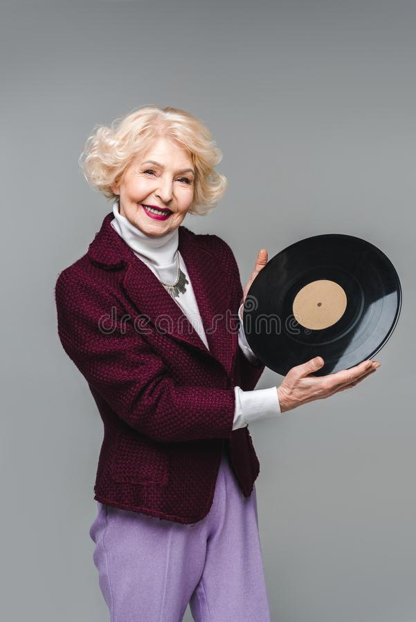 beautiful senior woman holding vinyl disc royalty free stock images