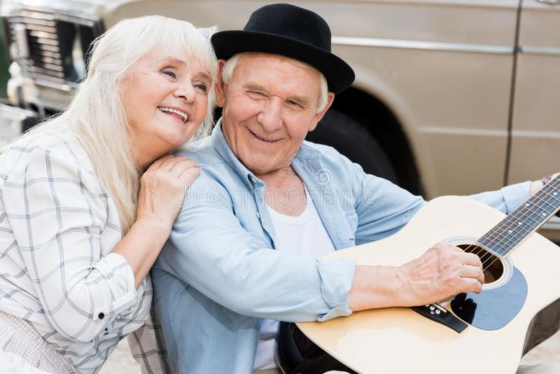 Beautiful senior woman hugging man playing guitar against beige. Vintage car stock image