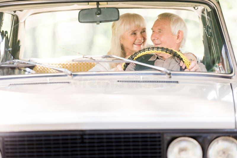 Beautiful senior woman hugging man. In vintage car royalty free stock images