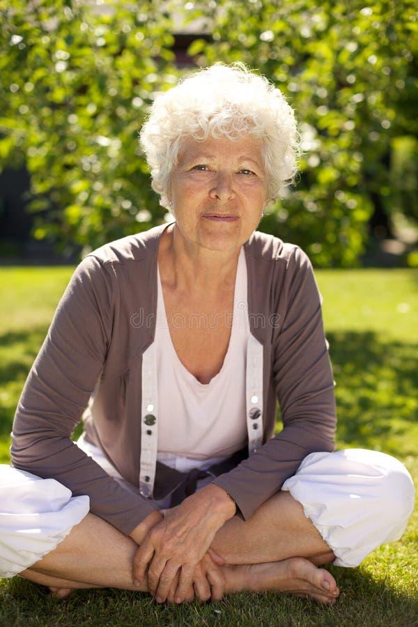 Beautiful senior woman sitting in her garden stock photo
