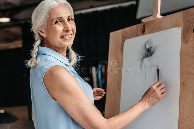 beautiful senior woman smiling at camera while drawing with pencil on easel stock image