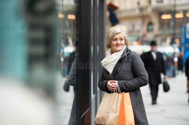 Beautiful senior woman window shopping in the city. Winter stock images