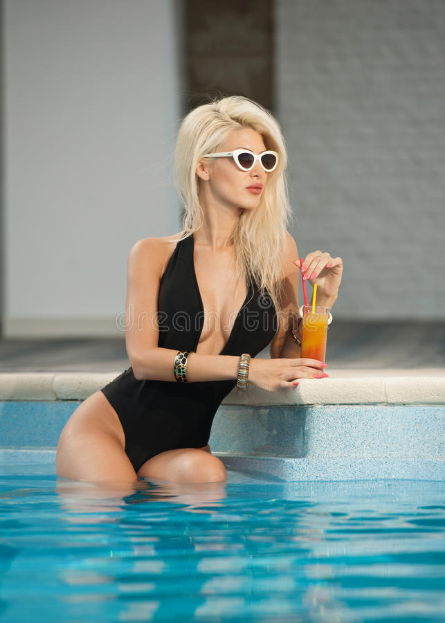 Beautiful sensual blonde with fashionable sunglasses relaxing in the pool with a juice. Attractive long hair woman in black royalty free stock photography