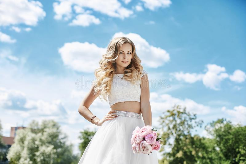 Beautiful and sensual blonde model girl with body in stylish tulle skirt and in fashionable blouse, with bouquet of flowers i. N her hand posing outdoors with stock photo