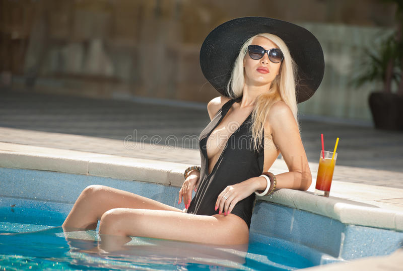 Beautiful sensual blonde with sunglasses and black hut relaxing in the pool with a juice. Attractive long hair woman in black. Low-cut swimsuit at swimming pool royalty free stock photo