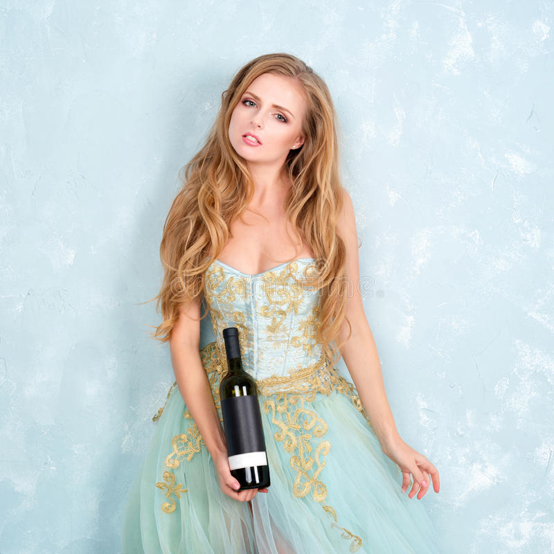 Beautiful sensual blonde woman in gorgeous long dress holding bottle of wine. Young girl celebrating. Proposing product. Advertisement royalty free stock photography