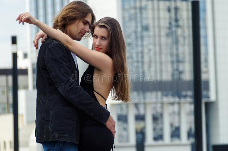 Beautiful sensual elegant couple stands on a city street and embraces stock photos
