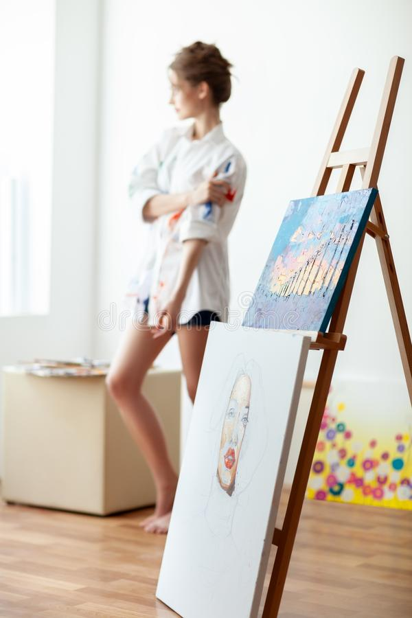 Beautiful sensual female artist posing in her art studio, sitting on chair. stock images