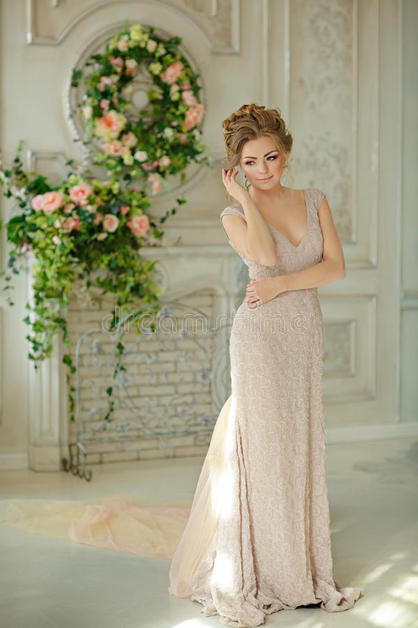 Beautiful sensual girl blond in beige dress gently smiles in the royalty free stock photography