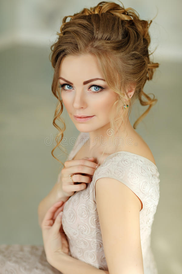Beautiful sensual girl blonde in beige dress and with high hairdo. Close-up portrait stock image