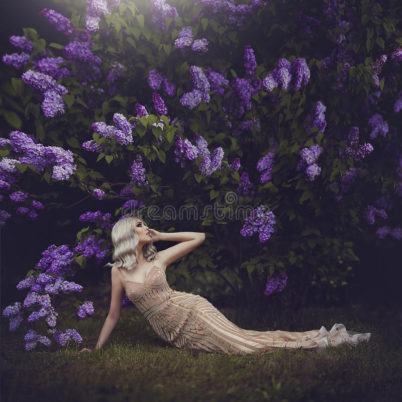Beautiful sensual girl blonde in spring. Spring style. Blossoming spring garden. A young girl in a gold dress lies under royalty free stock photography