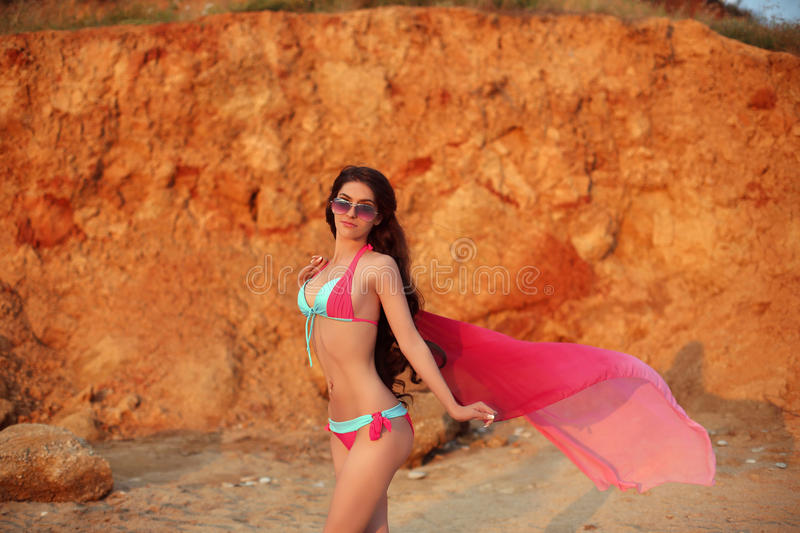 Beautiful sensual slim girl model in bikini and fashion sunglasses with blowing scarf on the beach at sunset. royalty free stock photography
