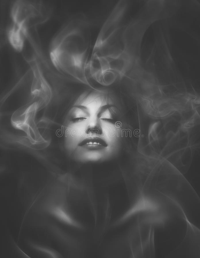 Beautiful sensual woman with closed eyes wrapped in smoke or mis. T royalty free stock photo