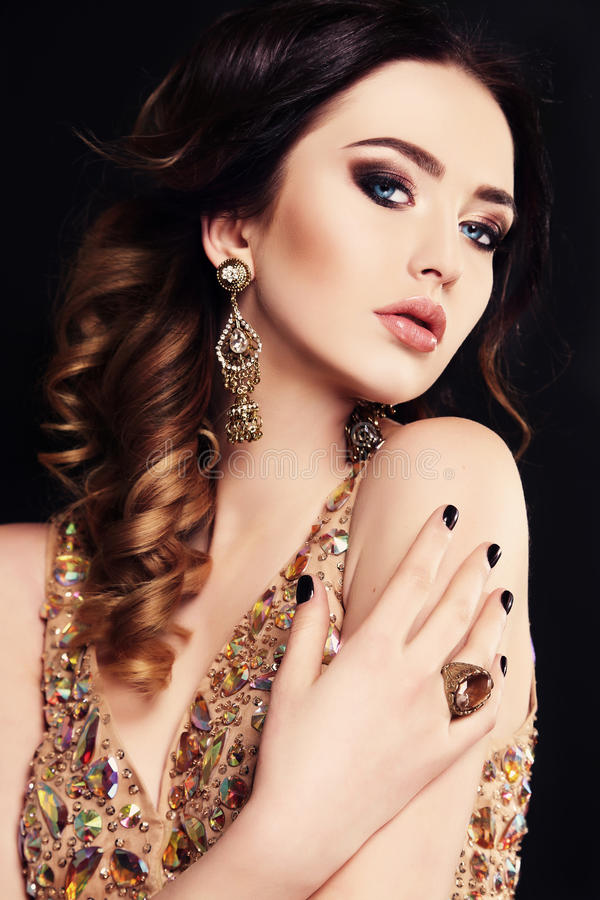 Beautiful sensual woman with dark hair and bright makeup, with bijou. Fashion studio photo of beautiful sensual woman with dark hair wearing luxurious sequin stock photo