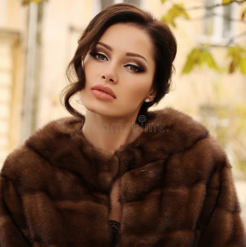 Beautiful sensual woman with dark hair wears luxurious fur coat royalty free stock image