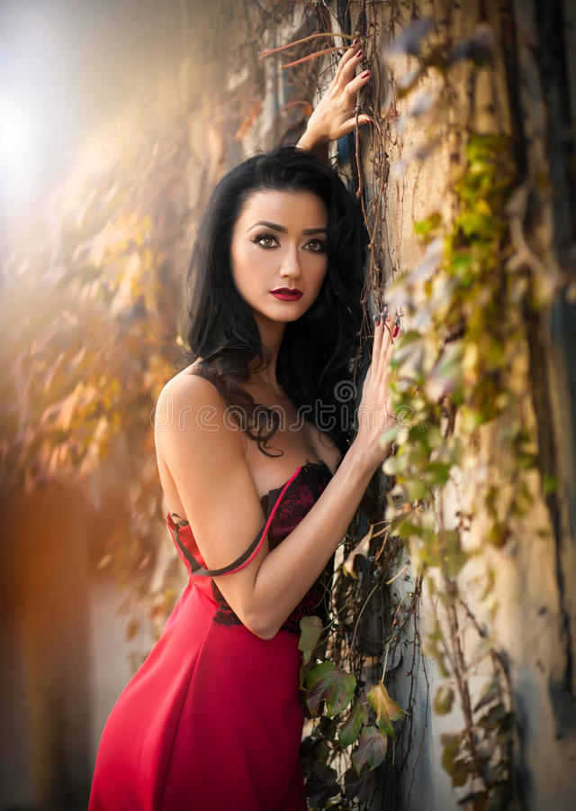 Beautiful sensual woman in red dress posing in autumnal park. Young brunette woman daydreaming near a wall with rusty leaves. During fall season. Dark hair royalty free stock photos