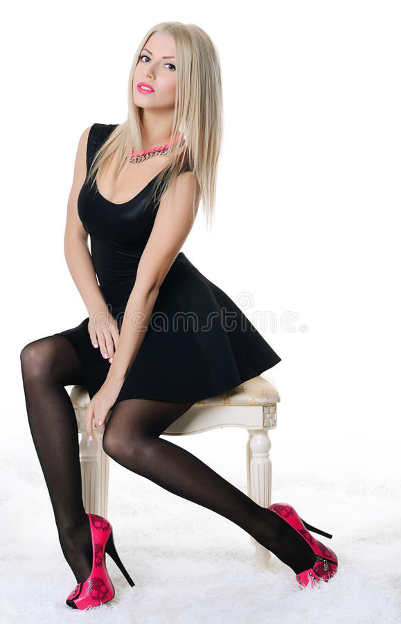 Beautiful sensual woman sits on chair stock photo