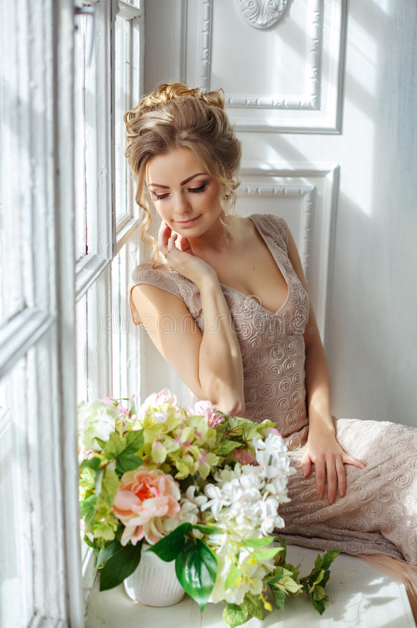 A beautiful sensual young blond woman in a beige dress sits on a royalty free stock photo