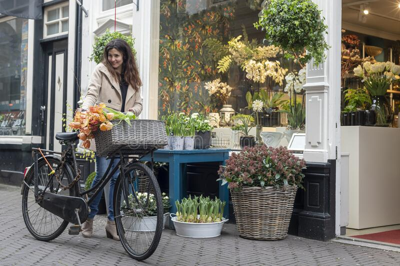 Beautiful sensuality elegance lady on bicycle. Beautiful sensuality elegance lady, brown happy, fun cheerful smiling woman in brown jacket, black t-shirt and royalty free stock image