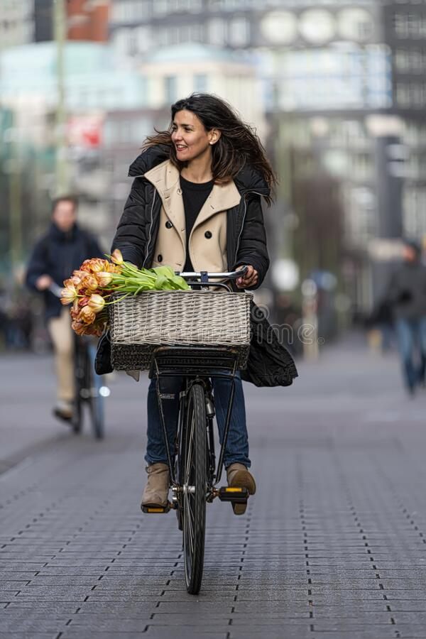 Beautiful sensuality elegance lady on bicycle. Beautiful sensuality elegance lady, brown happy, fun cheerful smiling woman in brown jacket, black t-shirt and stock images