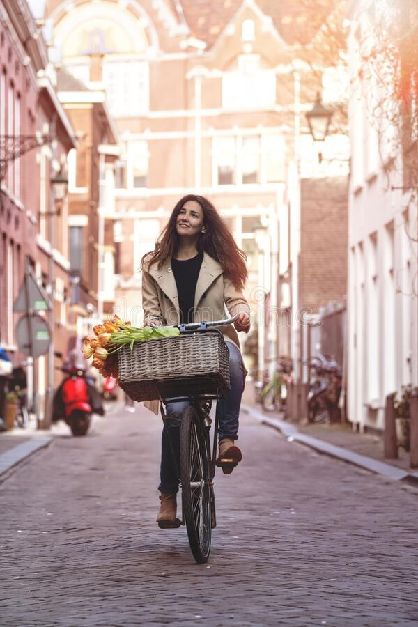 Beautiful sensuality elegance lady on bicycle. Beautiful sensuality elegance lady, brown happy, fun cheerful smiling woman in brown jacket, black t-shirt and royalty free stock photos