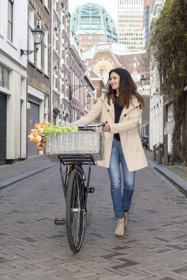 Beautiful sensuality elegance lady on bicycle. Beautiful sensuality elegance lady, brown happy, fun cheerful smiling woman in brown jacket, black t-shirt and stock photos