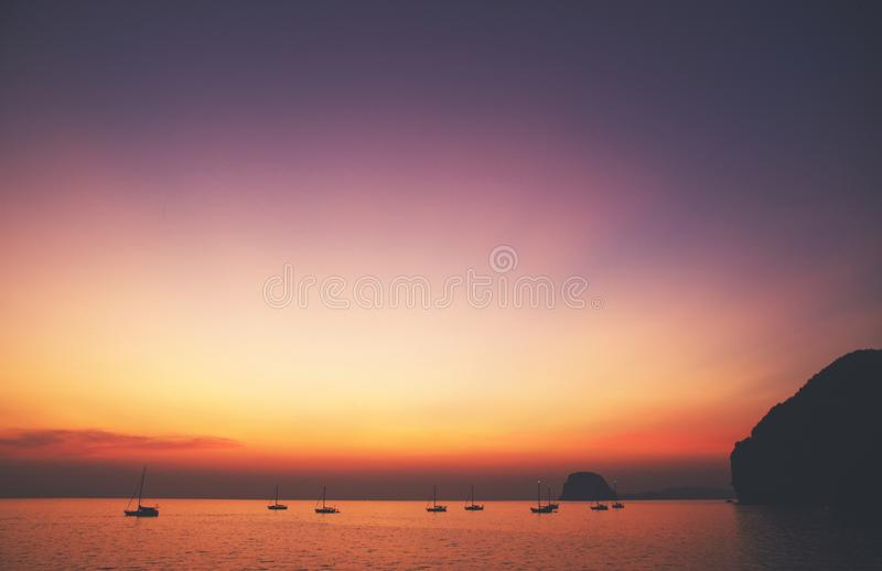 Beautiful and serene sunset with horizon. Beautiful and serene sunset view over a lagoon/bay with couple of yachts and islands in distance; Small, perfect stock photography