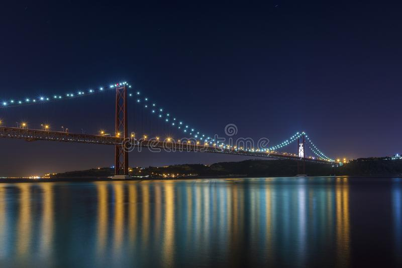 Beautiful and serene view of the Tagus River and the 25 of April Bridge Ponte 25 de Abril at night, in Lisbon. Portugal; Concept for visit Lisbon stock photo