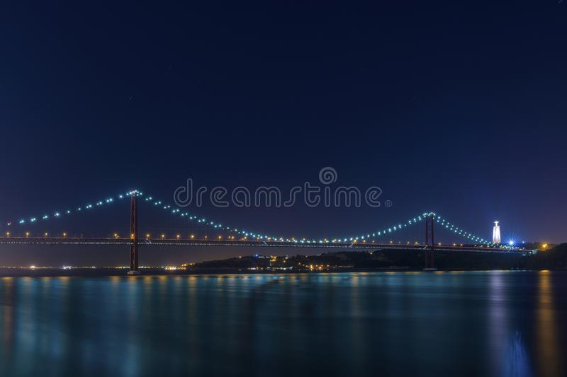 Beautiful and serene view of the Tagus River and the 25 of April Bridge Ponte 25 de Abril at night, in Lisbon. Portugal royalty free stock image