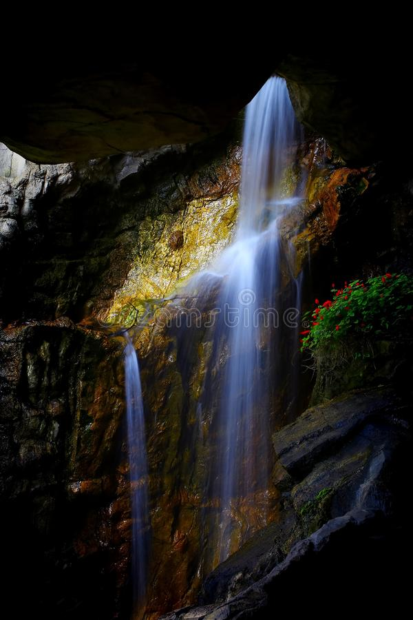 Underground cave waterfall between rock formations royalty free stock photo