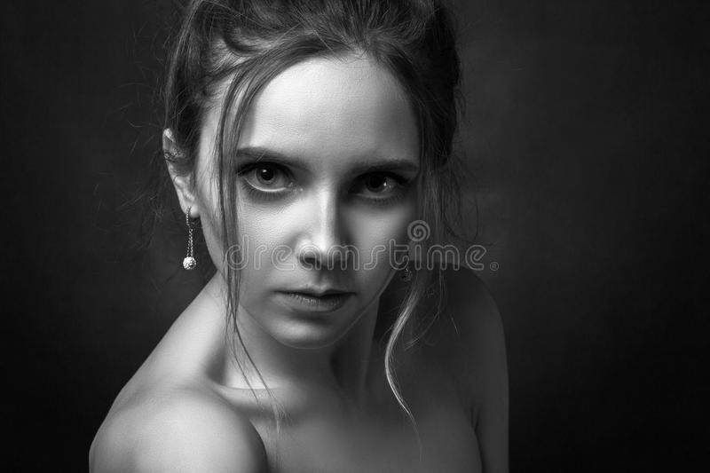 Serious sad woman. Beautiful serious pensive young blond female portrait on black background looking at camera, monochrome royalty free stock photos