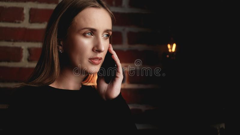 Beautiful serious young woman standing against brick wall and using cellphone stock photos