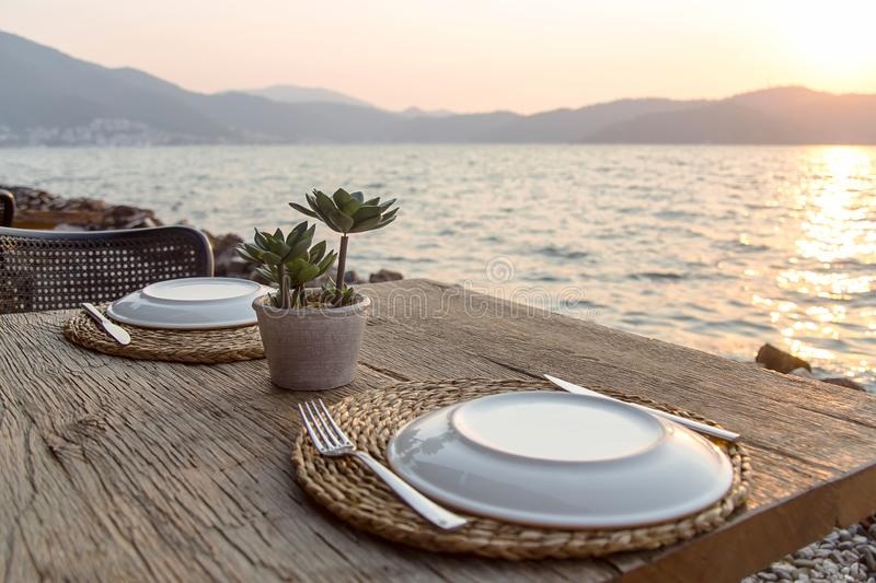 Travel table for lunch or dinner by the sea. Beautiful served table of a modern cafe by the sea with dishes and flowers. Stylish restaurant for dinner on stock photography