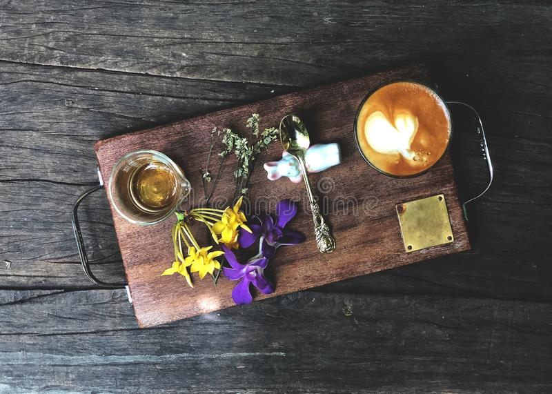 Beautiful serving size of coffee, Heart shape latte art , spoon, tea glass and flower on the wooden tray. Vintage style and  dark light royalty free stock images
