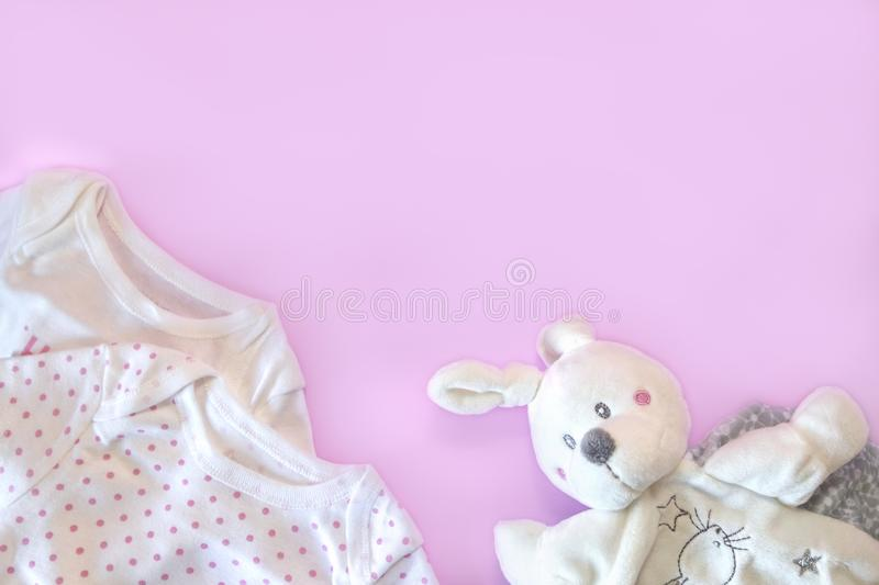 Beautiful set baby accessories - newborn baby clothes and funny toys on pink background. Copy space, flat lay, top view royalty free stock image