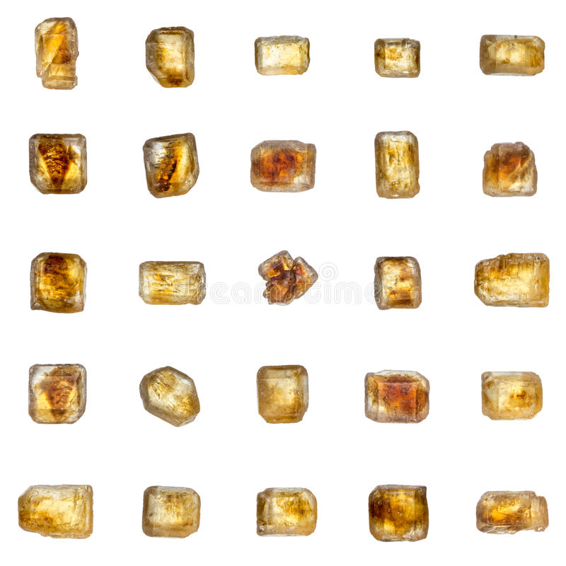 Beautiful set of 25 big golden-brown crystals of cane sugar isolated over white stock photography