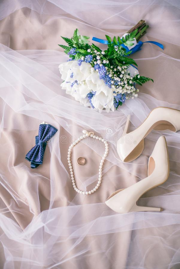 Beautiful set of women`s and groom`s wedding accessories. Bride`s morning. Bride`s bouquet of white tulips and blue flowers stock photography