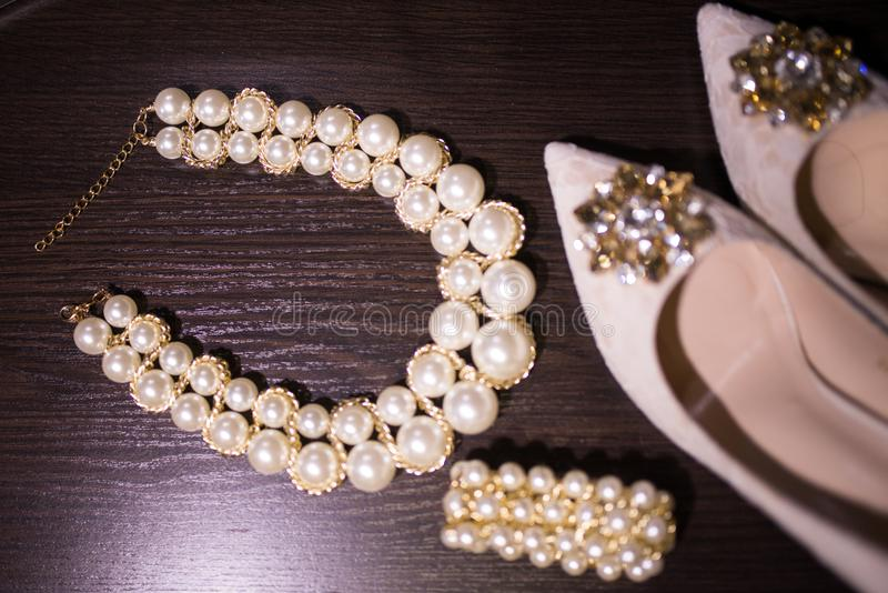 Beautiful set of women`s wedding accessories. Pearl necklace in focus, beige shoes with shiny stones on them, and a bracelet on th. E wooden background stock photo