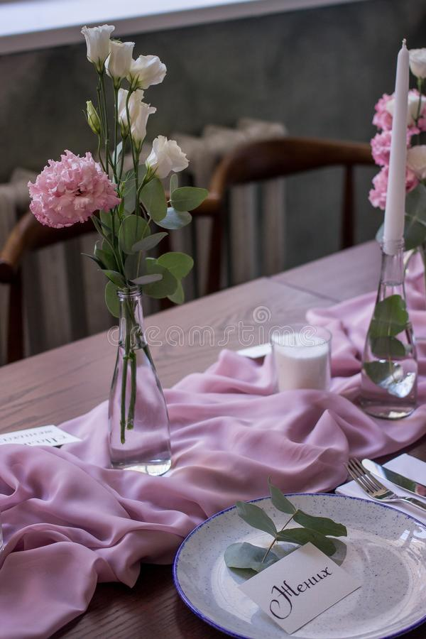 Beautiful setting of wedding party in restaurant. Tables and chairs decorated with flowers and fabrics gently pink in color stock photography
