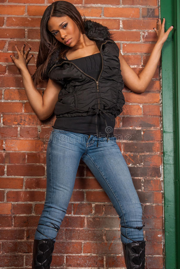 Super bad black lady wearing tight jeans and long boots with thick body and gorgeous face.