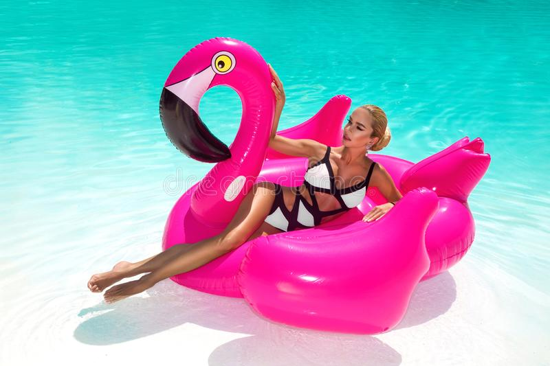 Beautiful sexy, amazing young woman in a swimming pool sitting on an inflatable pink flaming and laughing, tanned body, long hair royalty free stock photo