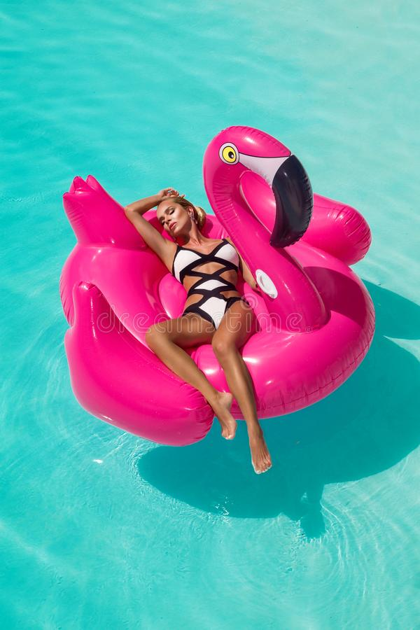 Beautiful sexy, amazing young woman in a swimming pool sitting on an inflatable pink flaming and laughing, tanned body, long hair royalty free stock image