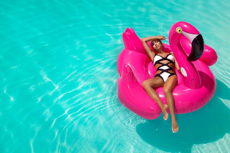 Beautiful sexy, amazing young woman in a swimming pool sitting on an inflatable pink flaming and laughing, tanned body, long hair royalty free stock photography