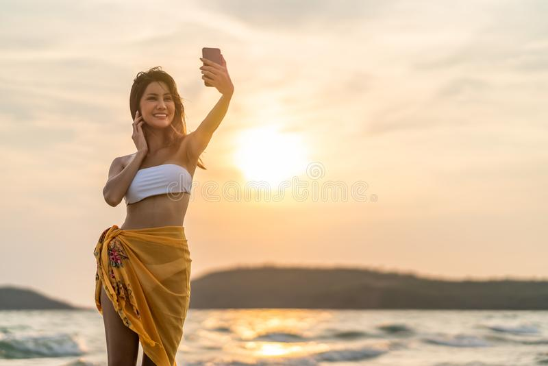 Beautiful sexy Asian girl smiling taking selfie photo or live video call, using smartphone on beach vacation at sunset royalty free stock image