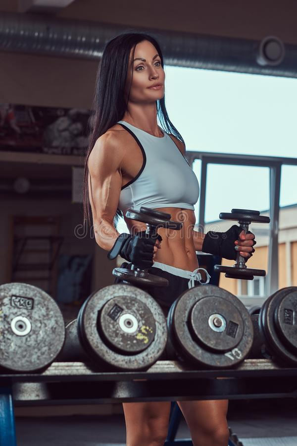 A beautiful athletic brunette female in a sportswear, doing exercise on a biceps near the counter with dumbbells i royalty free stock image