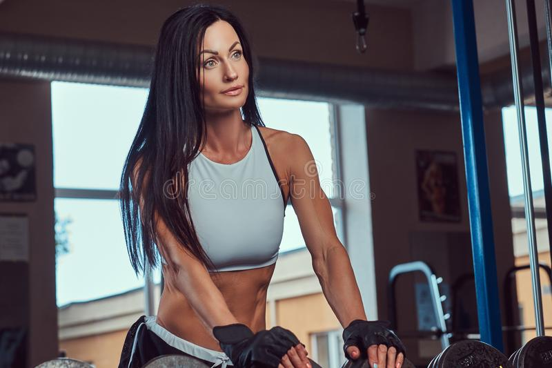 Beautiful athletic brunette female in a sportswear standing near the counter with dumbbells in the gym. royalty free stock photo